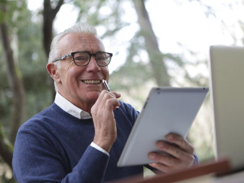 Photo of an elderly man. He is sitting by a window, in front of a computer, reading from a pad of paper
