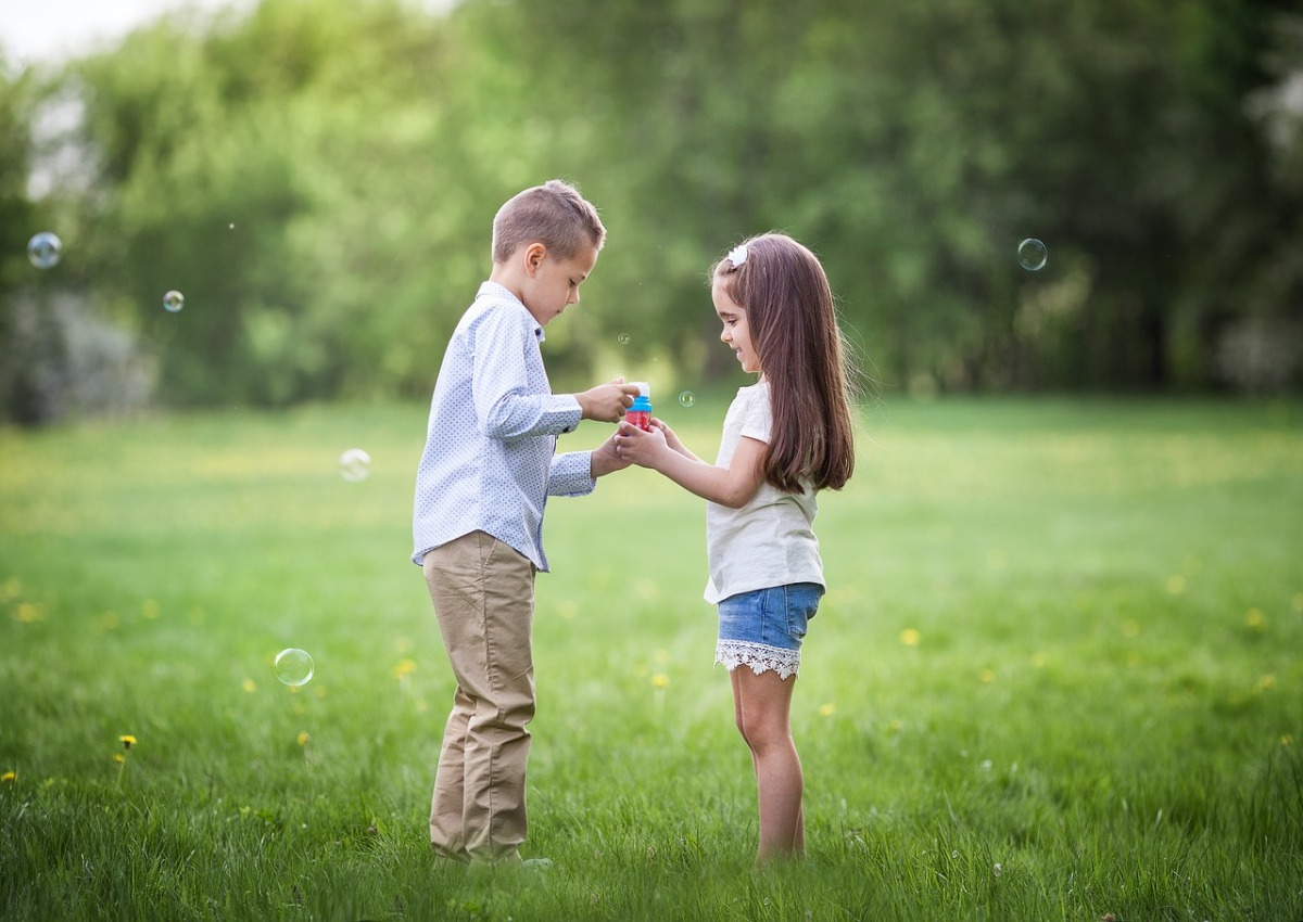 A photo of a boy, standing talking to a girl. They appear to be friends.