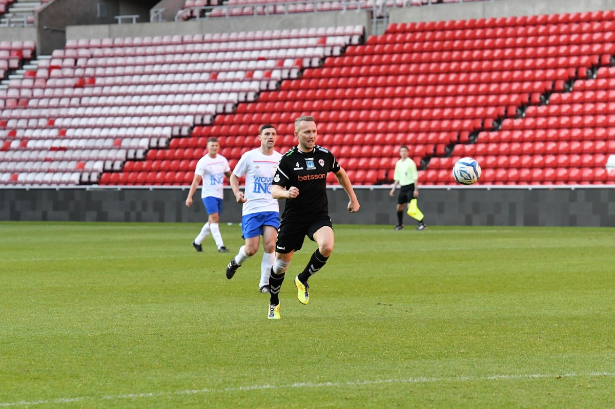 Photo of a professional soccer match being played in an empty stadium.