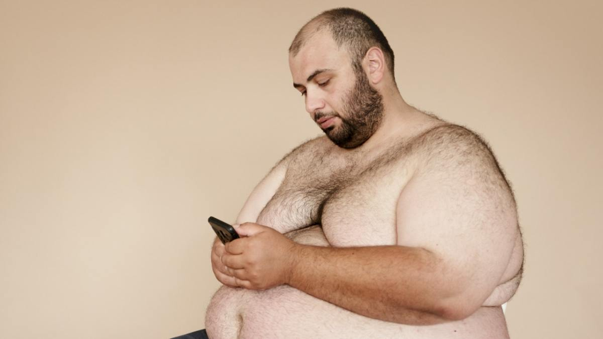Photo of a fat man, topless, checking his phone.