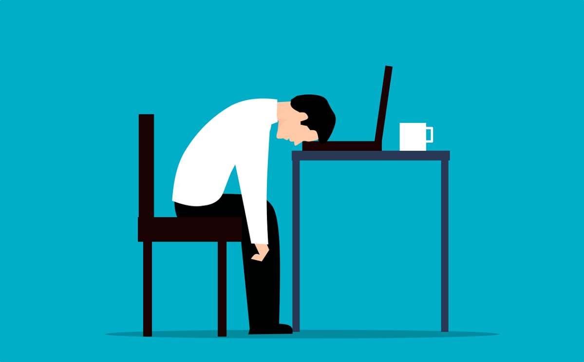 Clipart image of a man at work, slumped over his desk.