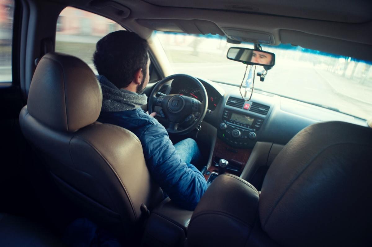 Photo of a man driving a car.